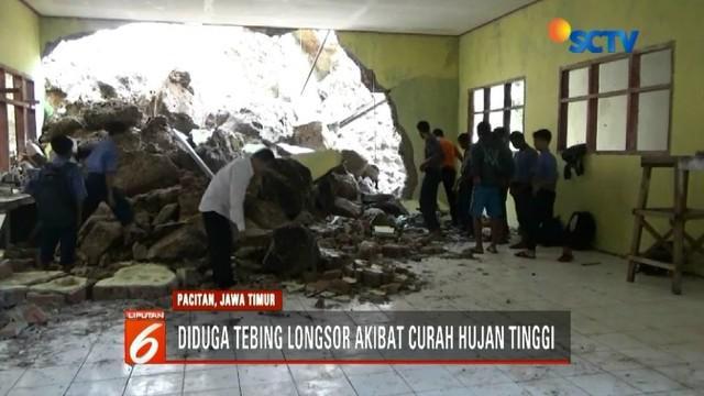 Akibat hujan deras yang mengguyur Pacitan, Jawa Timur, sebuah tebing longsor. Material longsor berupa tanah dan batu menimpa dinding bangunan sebuah sekolah.