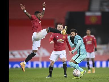 Pemain Manchester United, Fred (kiri) berusaha menghadang laju pemain Liverpool, Mohamed Salah pada laga babak keempat FA Cup 2020-21 di Old Trafford, Senin (25/01/2021). (Foto: AP/Pool/Laurence Griffiths)