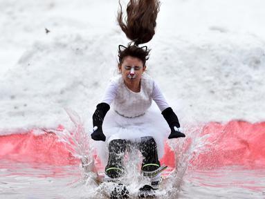Seorang peserta dengan mengenakan kostum melompat ke dalam kolam sebagai bagian dari kompetisi komik 'Californication 9.0' di kota Logoisk, utara Minsk, Belarus, 7 April 2019. Sebanyak 8 peserta dengan kostum unik berseluncur salju untuk merayakan  akhir musim dingin. (Sergei GAPON / AFP)