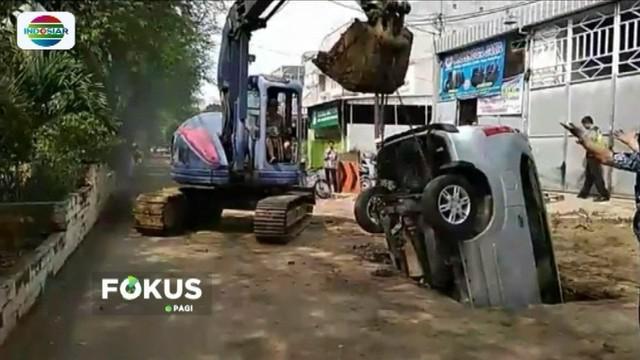 Sebuah mobil minibus yang hendak parkir terperosok ke lubang resapan air, di Jalan Dokter Susilo, Tanjung Duren, Jakarta Barat. Beruntung sang pengemudi selamat.