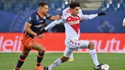 Gelandang AS Monaco, Sofiane Diop melepaskan diri dari hadangan bek Montpellier, Daniel Congre dalam laga lanjutan Liga Prancis 2020/21 pekan ke-20 di Mosson Stadium, Montpellier, Jumat (15/1/2021). AS Monaco menang 3-2 atas Montpellier. (AFP/Pascal Guyot)