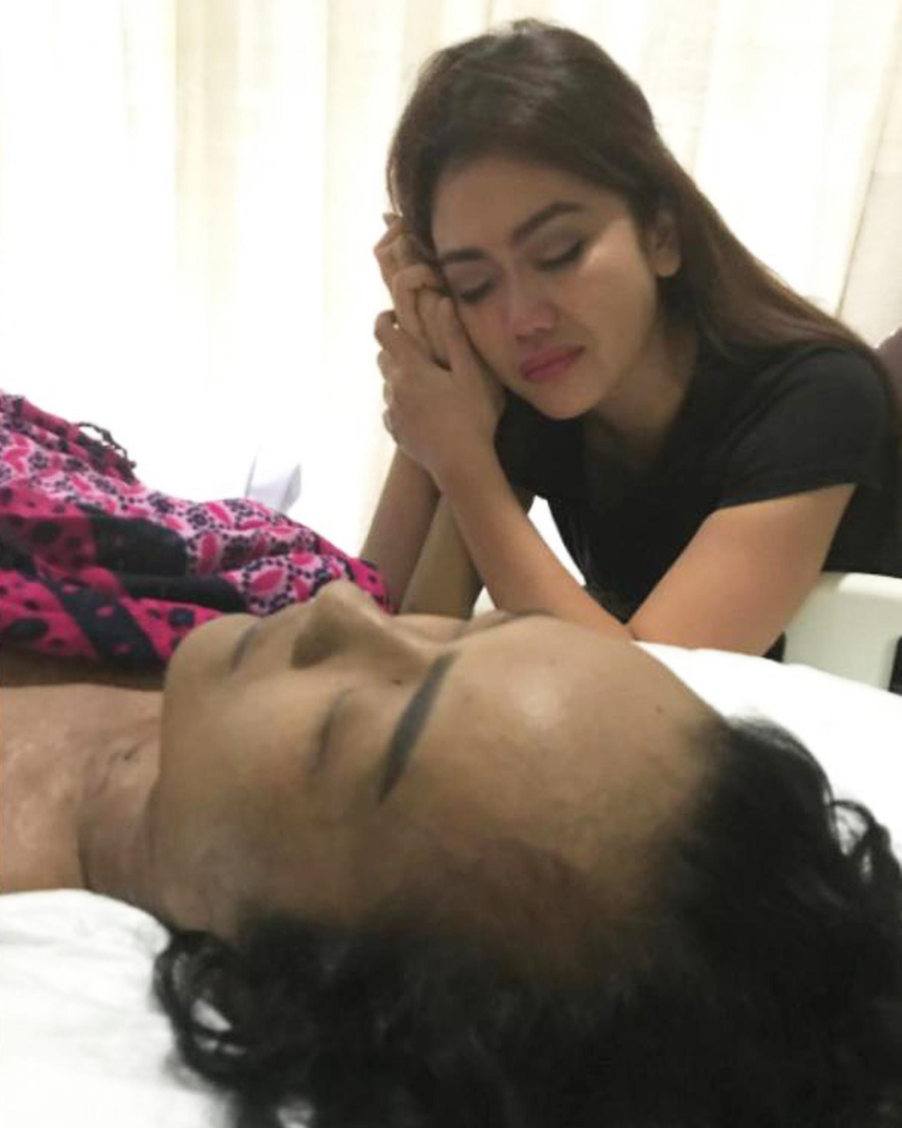 Anggia adik Julia Perez menggenggam tangan kakaknya yang sedang terbaring di RSCM, Jakarta. (Instagram/ anggitheperez)