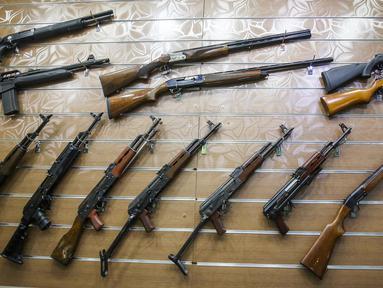 Bermacam-macam senapan tergantung di dinding sebuah toko senjata berlisensi di ibu kota Irak, 24 September 2018. Pertama kalinya selama beberapa dekade terakhir, senjata semi otomatis dan pistol dapat dibeli secara legal di Baghdad. (AFP/AHMAD AL-RUBAYE)