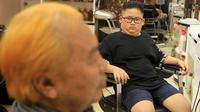 Le Phuc Hai, 66 tahun (kiri) dan To Gia Huy , 9 tahun, setelah rambut mereka dipangkas dengan gaya pemimpin Korea Utara Kim Jong-un dan Presiden Amerika Serikat, Donald Trump di sebuah salon di Hanoi, Vietnam, 19 Februari 2019. (AP/Hau Dinh)