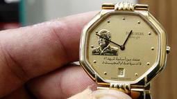 Jam tangan dengan hiasan bergambar mantan Presiden Irak, Saddam Hussein di Baghdad, Irak (28/12). Kekuasaannya berakhir setelah Irak diserang oleh pasukan koalisi yang dipimpin Amerika Serikat pada 2003. (AFP/Sabah Arar)