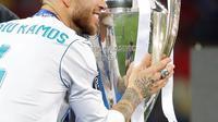 Kapten Real Madrid Sergio Ramos menyentuh trofi setelah memenangkan pertandingan final Liga Champions antara Real Madrid dan Liverpool di Stadion NSK Olimpiyskiy, Ukraina (26/5). (AP/Sergei Grits)
