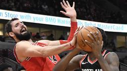 Pebasket Chicago Bulls, Nikola Mirotic, berusaha menghadang pebasket Portland Trail Blazers, Al-Farouq Aminu, pada laga NBA di Stadion United Center, Selasa (2/1/2018). Bulls kalah dari Blazers dengan skor 120-124. (AP/David Banks)