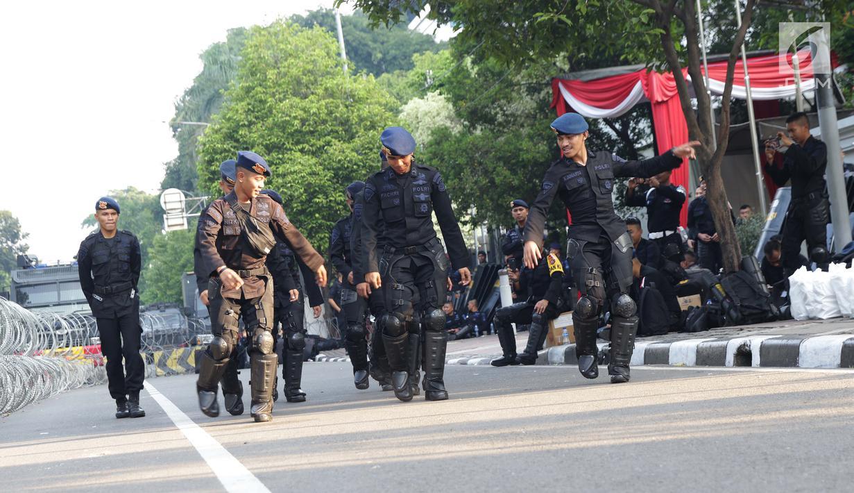 Personel Brimob menari bersama disela-sela berjaga di depan Gedung Mahkamah Konstitusi (MK), Jakarta, Selasa (25/6/2019). Jelang sidang pembacaan putusan akan digelar pada Kamis (27/6), penjagaan di sekitar Gedung Mahkamah Konstitusi diperketat. (Liputan6.com/Helmi Fithriansyah)