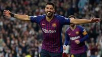 Penyerang Barcelona Luis Suarez berselebrasi setelah rekannya, Raphael Varane mencetak gol bunuh diri pada laga leg kedua semifinal Copa del Rey melawan Real Madrid di Stadion Santiago Bernabeu, Rabu (27/2). Barcelona menang telak 3-0. (AP/Andrea Comas)