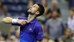 Petenis Serbia, Novak Djokovic merayakan kemenangan atas Matteo Berrettini dari Italia pada perempat final AS Terbuka 2021 di Arthur Ashes Stadium, New York, Kamis (9/9/2021). Petenis nomor satu dunia itu melaju ke semifinal AS Terbuka usai menang 5-7, 6-2, 6-2, 6-3. (Elsa/Getty Images/AFP)