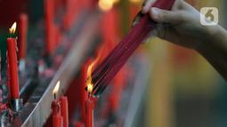Umat Buddha membakar dupa sesaat sebelum ritual sembahyang di Vihara Buddha Dharma dan 8 Pho Sat, Kabupaten Bogor, Jawa Barat, Rabu (26/5/2021). Umat Buddha melakukan sembahyang peringatan Hari Raya Waisak di Vihara Buddha Dharma dan 8 Pho Sat  (Liputan6.com/Helmi Fithriansyah)