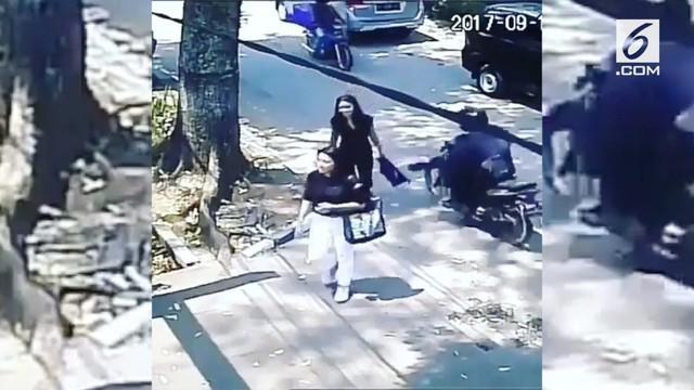 Seorang wanita yang sedang berjalan kaki dijambret oleh seorang pengendara motor. Kejadian ini terekam CCTV sebuah gedung.