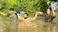 Personil TNI mengevakuasi warga saat banjir bandang  di Kabupaten Bone Bolango, Gorontalo (11/6/2020). Data sementara yang diterima dari BPBD Kabupaten Bone Bolango sekitar 1.078 kepala keluarga serta 5.407 jiwa terdampak banjir bandang. (Liputan.com/Arfandi Ibrahim)