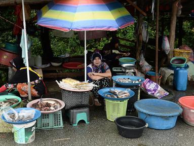 Sejumlah wanita muslim menjual ikan di pinggir jalan di Narathiwat, provinsi selatan Thailand (19/12). Narathiwat adalah tiga provinsi Thailand yang mempunyai jumlah umat Muslim yang besar. (AFP Photo/Lillian Suwanrumpha)