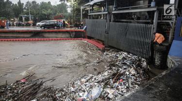 Seorang petugas membersihkan sampah yang menyangkut di Pintu Air Manggarai, Jakarta, Senin (5/2). Volume sampah terus meningkat lebih dari 200 ton. (Liputan6.com/Faizal Fanani)