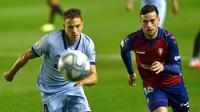 Bek Atletico Madrid, Santiago Arias, berebut bola dengan penyerang Osasuna, Jose Arnaiz, pada laga lanjutan La Liga pekan ke-29 di Stadion El Sadar, Pamplona, Kamis (18/6/2020) dini hari WIB. Atletico menang telak 5-0 atas Osasuna. (AFP/Ander Gillenea)