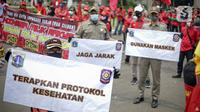 Petugas Satpol PP memegang poster imbauan protokol kesehatan COVID-19 saat unjuk rasa buruh di depan Gedung DPR, Jakarta, Selasa (17/11/2020). Pemerintah terus mengingatkan pentingnya 3M yaitu memakai masker, menjaga jarak, dan mencuci sebagai upaya pencegahan Covid-19. (Liputan6.com/Faizal Fanani)