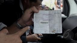 Petugas kantor Pos memperlihatkan tanda terima dua peti jenazah untuk Kedutaan Besar Australia yang dikirim oleh Bambang Saptono asal Solo, Jakarta, Senin (9/3/2015). Kedubes Australia menolak kiriman dua peti mati tersebut. (Liputan6.com/Andrian M Tunay)