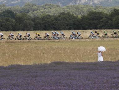 Seorang wanita dengan gaun dan payung putih menonton balapan Tour de France etape ke-19 dengan jarak tempuh 222,5 km dari Embrun menuju Salon-de-Provence, Prancis, (21/7/2017). (AP/Christophe Ena)