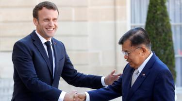 Presiden Prancis Emmanuel Macron (kiri) menyalami Wakil Presiden Indonesia Jusuf Kalla saat menghadiri KTT Paris: Ekstremisme Online di Istana Elysee, Paris, Prancis, Rabu (15/5/2019). Presiden Macron terlihat hangat saat menyambut Wapres Kalla. (REUTERS/Philippe Wojazer)
