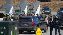 Petugas Polisi Mounted Royal Kanada saat menangkap tersangka di sebuah pom bensin di Enfield, Nova Scotia, Minggu (19/4/2020). Seorang pria bersenjata menewaskan lebih dari 10 orang dalam aksinya, termasuk seorang polisi wanita. (Tim Krochak/The Canadian Press via AP)