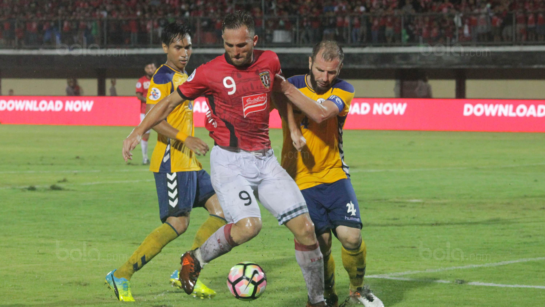 Striker Bali United, Ilija Spasojevic, menghindari kepungan pemain Tampines Rovers pada laga kualifikasi Liga Champions Asia di Stadion I Wayan Dipta, Gianyar, Selasa (16/1/2018). Bali United menang 3-1 atas Tampines Rovers.(Bola.com/Ronald Seger)