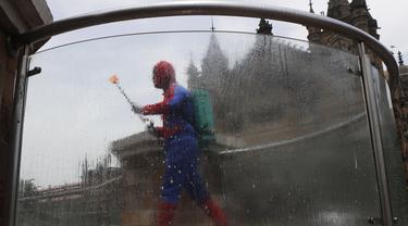Pekerja sosial India Ashok Kurmi berpakaian seperti Spider Man mendesinfeksi daerah di sekitar stasiun kereta Chhatrapati Shivaji Maharaj selama lockdown yang diberlakukan di Mumbai, Rabu (21/4/2021). Kegiatan tersebut dilakukan untuk mengekang penyebaran COVID-19 di Mumbai. (AP Photo/Rajanish Kakad