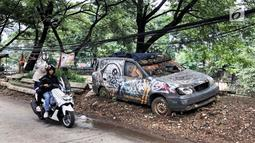 Pengendara motor melintas disamping sebuah mobil patroli Polsek Tanah Abang, Jakarta, Rabu (6/3). Mobil operasional merk KIA berkarat dan tidak tertutup terpal. (Liputan6.com/Fery Pradolo)