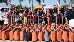 Sejumlah orang mengatarkan keluarga mereka bertolak ke Tanah Suci Mekah di Bandara Provinsi Narathiwat, Thailand, Kamis (4/7/2019). Jutaan umat muslim dari penjuru dunia akan bertolak menuju Mekah untuk melangsungkan ibadah haji. (Madaree TOHLALA/AFP)
