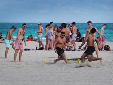Orang-orang bersenang-senang di pantai di Miami, Florida pada Selasa (16/3/2021). Mahasiswa telah tiba di daerah Florida Selatan untuk liburan musim semi tahunan. Para pejabat kota prihatin dengan kerumunan liburan musim semi saat pandemi COVID-19 terus berlanjut. (Joe Raedle/Getty Images/AFP)