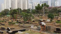 Pekerja membersihkan makam di TPU Karet Bivak, Jakarta, Kamis (26/7). Wagub DKI Jakarta Sandiaga Uno menyatakan akan mencari dan memerbanyak area TPU di Ibukota yang akan dimasukkan dalam anggaran Pemprov DKI tahun depan. (Liputan6.com/Immanuel Antonius)