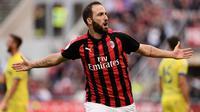 Striker AC Milan Gonzalo Higuain merayakan gol ke gawang Chievi Verona pada laga Serie A di San Siro, Minggu (7/10/2018). (AFP/Marco Bertorello)