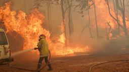 Seorang petugas pemadam kebakaran menangani kobaran api di dekat Wooroloo, timur laut Perth, Australia, Selasa (2/1/2021). Asap dan api dari kebakaran hutan membakar kota terbesar keempat di Australia ini, di tengah pemberlakuan lockdown virus corona COVID-19. (Evan Collis/DFES via AP)