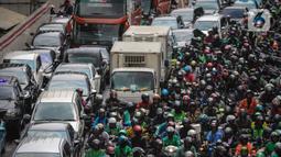 Kendaraan terpaksa berjalan tersendat di Jalan Rasuna Said, Kuningan, Jakarta, Rabu (22/1/2020). Kemacetan di depan Kantor Kemenkumham ini  imbas dari unjuk rasa warga Tanjung Priok yang memprotes dan menuntut Menkumham Yasonna Laoly minta maaf. (Liputan6.com/Faizal Fanani)