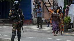 Seorang personel keamanan Sri Lanka berjaga-jaga di pos pemeriksaan saat negara itu bersiap untuk lockdown di Kolombo, Selasa (25/5/2021). Sri Lanka bersiap menerapkan lockdown ketat selama dua minggu untuk menekan penyebaran corona Covid-19. (ISHARA S. KODIKARA / AFP)