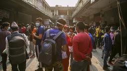 Calon penumpang berdebat dengan staf bus untuk mendapatkan tiket kembali ke desa mereka sehari sebelum lockdown di Kathmandu, Rabu (28/4/2021). Puluhan ribu orang meninggalkan ibu kota Nepal sehari menjelang lockdown yang diberlakukan karena melonjaknya kasus COVID-19. (AP Photo/Niranjan Shrestha)