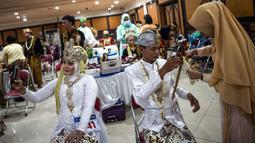Pasangan pengantin bersiap mengikuti nikah massal di Surabaya, Jawa Timur, Rabu (18/12/2019). Sebanyak 60 pasangan pengantin mengikuti nikah massal yang digelar Dinas Sosial Kota Surabaya. (JUNI KRISWANTO/AFP)