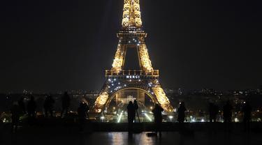"Awak media berdiri di depan Menara Eiffel dengan tulisan 'Merci"" (terima kasih) yang terpampang di Paris, Jumat (27/3/2020). Menara Eiffel menampilkan pesan dukungan dan terima kasih kepada tenaga kesehatan di Prancis yang berada di garda depan memerangi pandemi COVID-19.  (AP/Thibault Camus)"
