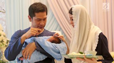 Pasangan selebritis Adi Nugroho dan Donita memotong rambut anak kedua mereka, Parvaiz Farezell Shaquill Nugroho saat aqiqah di Kebayoran View, Tangerang Selatan, Kamis (18/1). Namun, keduanya mengaku galau. (Liputan6.com/Herman Zakharia)