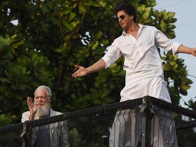 Aktor Bollywood, Shah Rukh Khan (kanan) disaksikan pembawa acara televisi AS, David Letterman menyapa para fans yang berkumpul di depan rumahnya pada perayaan Idul Fitri di Mumbai, Rabu (5/6/2019). Shah Rukh Khan tetap melakukan tradisi menyapa penggemar dari balkon atas rumahnya (SUJIT JAISWAL/AFP)