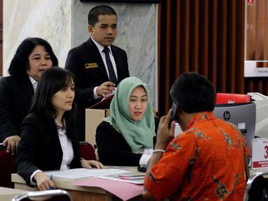 Petugas Mahkamah Konstitusi (kiri) melayani penggugat yang mendaftar di tempat sarana prasarana dukungan penanganan perkara perselisihan hasil Pilgub Serentak 2018 di Gedung Mahkamah Konstitusi, Jakarta, Kamis (5/7). (Liputan6.com/Johan Tallo)