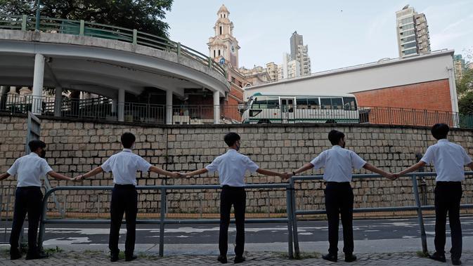 Para siswa saling memegang tangan mengelilingi St. Paul's College di Hong Kong, Senin (9/9/2019). Aksi dilakukan para siswa yang masih berseragam sekolah sebagai bentuk dukungan terhadap demonstran anti pemerintah setelah bentrokan yang terjadi pada akhir pekan lalu. (AP/Kin Cheung)