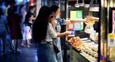 Dua wanita membeli makanan di pedagang kaki lima di Haikou, ibu kota Provinsi Hainan, China selatan (26/3/2020). Provinsi Kepulauan Hainan di China selatan pada Selasa (24/3) mencatatkan penurunan jumlah kasus penyakit coronavirus baru (COVID-19) yang ada menjadi nol. (Xinhua/Guo Cheng)