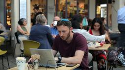 Seorang pria mengecek laptopnya di kafe di Abima Square di kota Tel Aviv, Israel (20/5/2021).  Israel dan dua kelompok bersenjata utama Palestina di Gaza, Hamas dan Jihad Islam, menyetujui gencatan senjata untuk mengakhiri konflik selama 11 hari. (AFP/Gideon Markowicz)