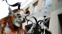 Sejumlah orang berkostum Krampuss selama parade di Munich, Jerman, Minggu (13/12). Dalam ceritanya Krampuss biasanya membawa cambuk hingga lonceng besar untuk menakut-nakuti anak-anak. (REUTERS/Michael Dalder)