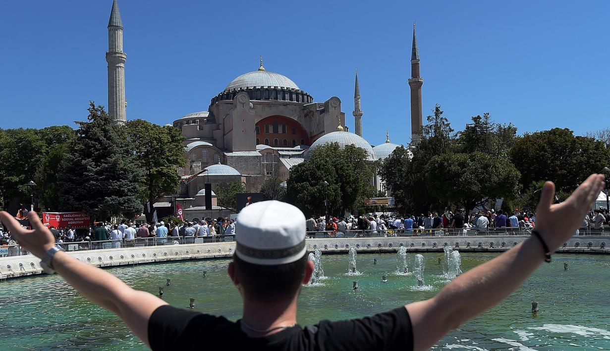 Seorang pemuda memberi isyarat saat menunggu di luar Hagia Sophia, Istanbul, Turki, Jumat (24/7/2020). Umat muslim melaksanakan salat Jumat pertama di Hagia Sophia dalam 86 tahun terakhir. (AP Photo/Yasin Akgul)