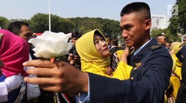 Perwira TNI-Polri menangis bersama orangtuanya usai dilantik Presiden Joko Widodo atau Jokowi di halaman Istana Merdeka, Jakarta Pusat, Selasa (16/7/2019). Jokowi melantik 781 perwira TNI-Polri di Istana Merdeka. (Liputan6.com/Angga Yuniar)