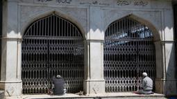 Muslim Kashmir berdoa di luar gerbang tertutup sebuah kuil muslim selama bulan puasa Ramadan di Srinagar, Kashmir yang dikuasai India (8/5/2020). (AP Photo/Mukhtar Khan)