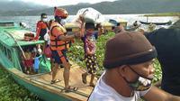 Keluarga dievakuasi ke tempat yang lebih aman di provinsi Camarines Sur, Filipina (31/10/2020). Keluarga yang tinggal di dekat kota-kota pesisir mulai pindah ke pusat-pusat evakuasi saat topan kuat mendekati negara itu. (Philippine Coast Guard via AP)