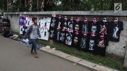 Penjual menjajakan kaos dagangannya di luar lokasi Konser Situs Budaya, kawasan Depok, Jawa Barat, Sabtu (3/3). Dalam Konser kali ini, Iwan Fals dan Band akan membawakan beberapa lagu andalan serta beberapa lagu daerah. (Liputan6.com/Arya Manggala)